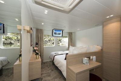 Lugar med seng, teppe, skap og små vinduer på nedre dekk. Foto.