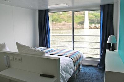 Lugar med seng, hylle, lampe, vindu og fransk balkong. Foto.
