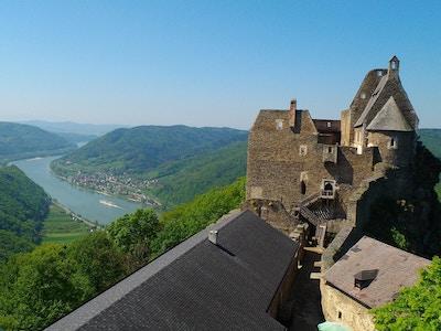 Panorama over elv og frodige åser med slottsruin i forgrunnen.