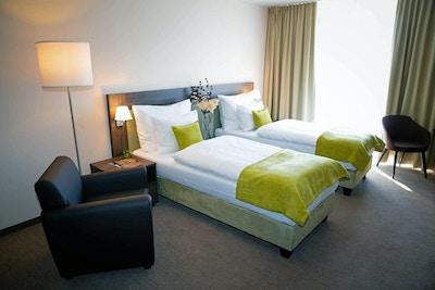 Hotellrom med to enkeltsenger og en lenestol