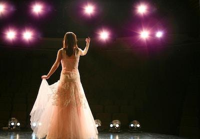 Kvinnelig operasanger bakfra på scenen i flott kjole