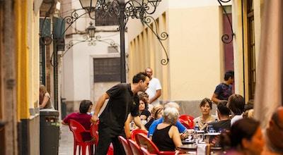 """""""Malaga, Spania - 8. august 2011: Folk sitter på atmosfæriske fortauskafeer i det historiske distriktet Malaga i Sør-Spania sent på ettermiddagen. En servitør kan sees som serverer drikke."""""""