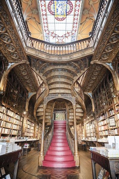 Interiør i bokhandel med utsmykket tak og flott trapp.