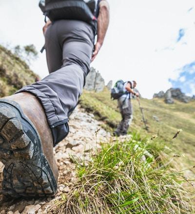 Turgåer går på en fjellsti. En annen turgåer er synlig i bakgrunnen.