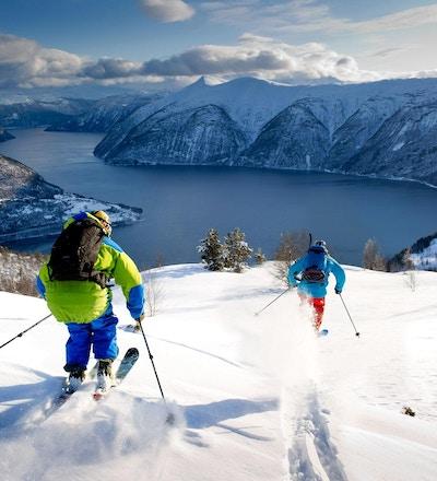 Skikjøring i løssnø nedover fjellene i retning fjorden