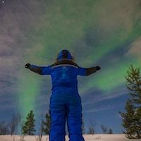 Turist med hette som ser på nordlyset på nattehimmelen i vinterlandskap, Kirkenes, Finnmark, Norge