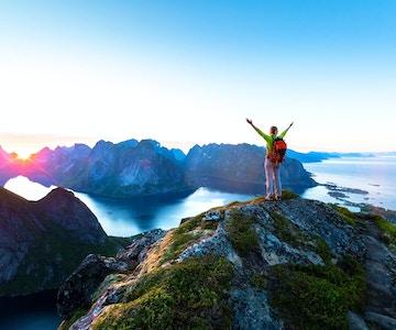 En fornøyd kvinnelig klatrer som nyter den vakre midnattsolen fra toppen på Reinebringen, som ligger ovenfor tettstedet Reine i Lofotskjærgården under den arktiske sommeren i Norge.