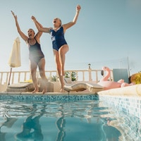 To eldre kvinner som holder hender og hopper ut i et svømmebasseng. De er glade og har det gøy.