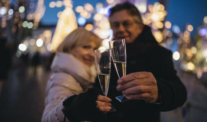 Portrett av et eldre par i sentrum en kald vinterdag. De skåler med champagne og smiler. Vi kan se julelys i ryggen.