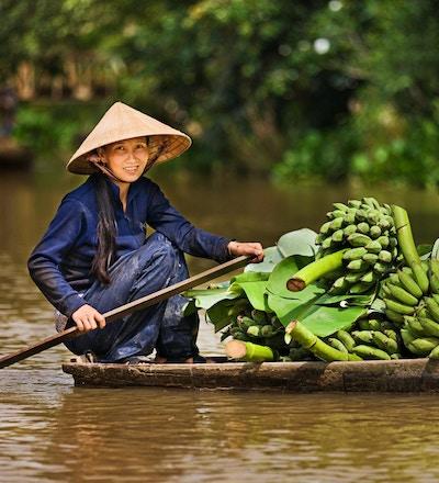 Vietnamesisk kvinne som ror en båt på Mekong elvedelta, Vietnam