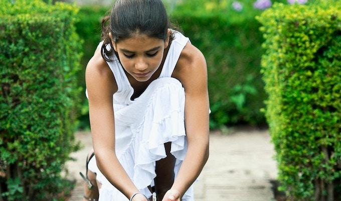 Liten jente som leker med ferskvann i hagene i Alhambra, Granada, Spania