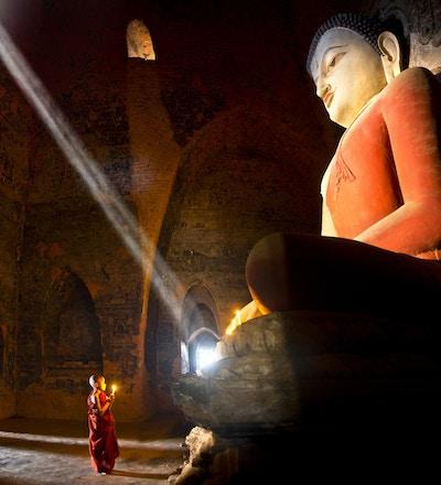 To unge buddhistmunker som ber inne i templet i Bagan, Myanmar