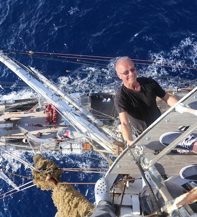 En mann som henger i masten på et skip