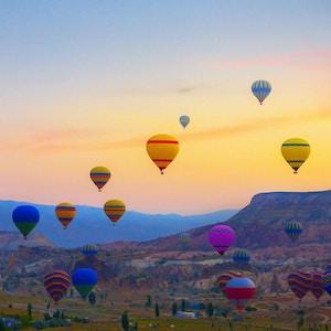 Luftballonger som lander på et fjell Cappadocia Goreme nasjonalpark i Tyrkia.