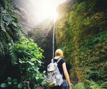 Ung kvinne som nyter fossen Caldeiré Verde mens hun vandretur på Madeira.