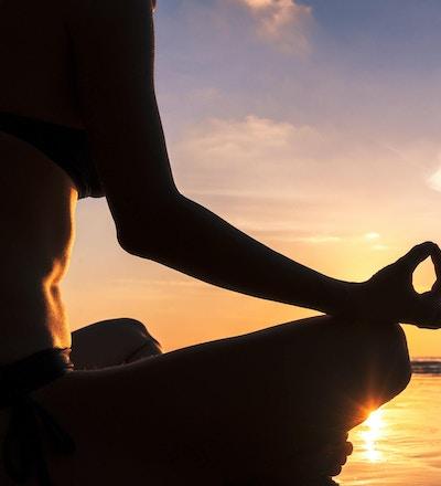 Ung kvinne som praktiserer yoga på stranden for velvære, nærbilde av hånden.