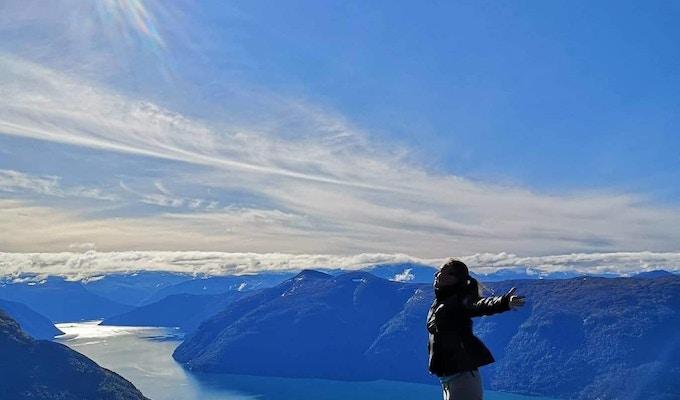 Kvinne med armene utstrakt mot sola på toppen av fjellet med fjord og fjell i bakgrunnen.