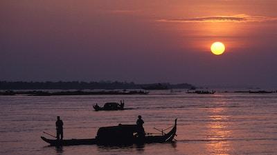 Tidlig morgenscene i Kambodsja. Fiskebåter glir utover vannet for morgenfangsten.