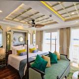 Suite med seng, vinduer, sofa, puter, møbler. Foto.