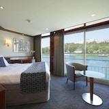 Suite på øvre dekk med dobbeltseng, sittegruppe, gulvteppe, panoramaviduer og fransk balkong