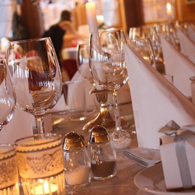 Bordet er dekket med duk, glass, telys og salt- og pepperbøsse