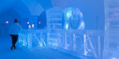 Mann som er kledd i vinterklær står ved baren laget av is inne i ishotellet