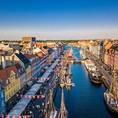 Urban kanal med seilskip, flankert av gater med danske flagg. Flyfoto.