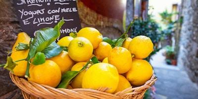 Flettkurv full av sitroner på den italienske gaten od Corniglia