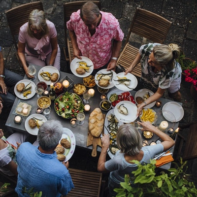 En gruppe voksne venner sitter rundt et utendørs spisebord og spiser og drikker. De snakker alle lykkelig og gleder seg over hverandres selskap. Bildet er tatt ovenfra, i Toscana, Italia.