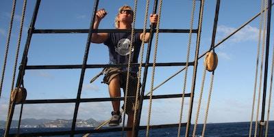 en mann klatrer opp til seilet