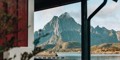 Utsikt mot sjø og fjell fra terrasse.