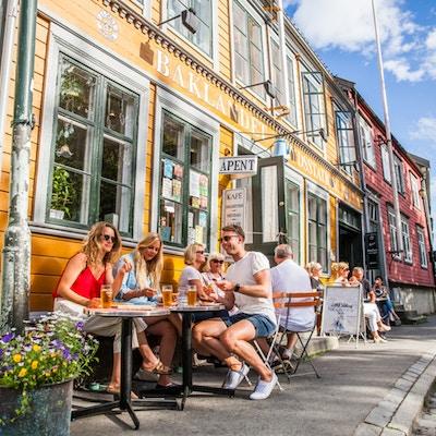 Mennesker sittende ved bord langs veggen i solskinn i lav trehusbebyggelse