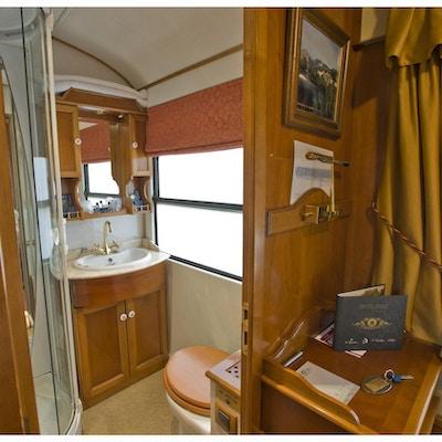 Åpen dør fra togkupeen inn til bad med vask, dusj og toalett.