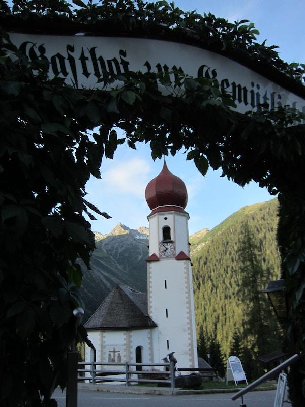 Kirke med fjell i bakgrunnen, alpene.
