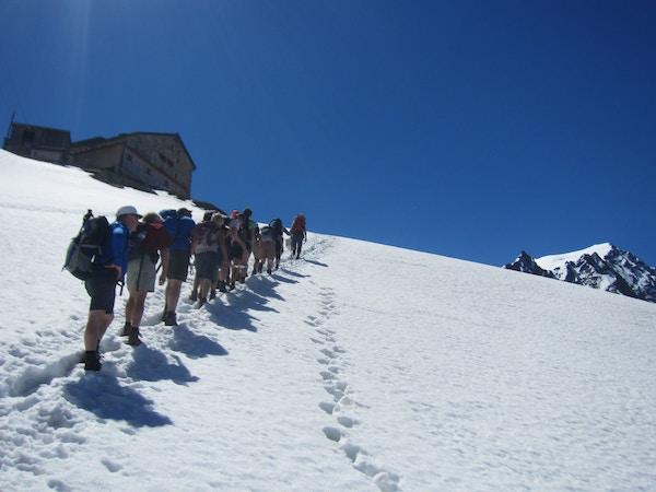 Mennesker vandrer på snø i alpene.