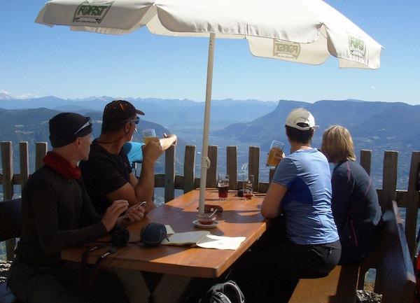 Mennesker på restaurant med storslagen utsikt i alpene.