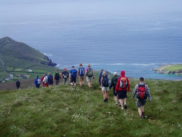 Turister på vandring ved kysten, Irland.