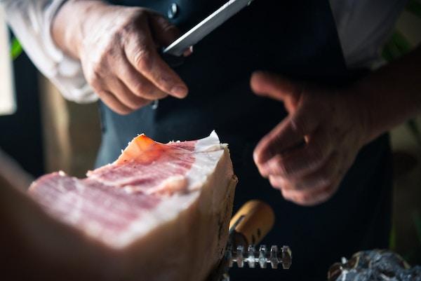 Mann skjærer opp italiensk skinke.