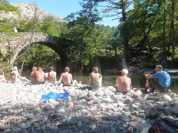 Mennesker sitter ved en elv på Korsika.