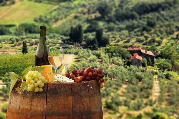 Vinflaske med oster og druer på en tønne utenfor en vingård.