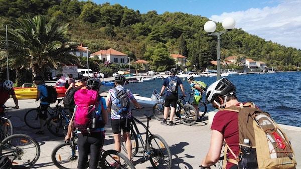 Mennesker med sykkel ved en kai i Kroatia.