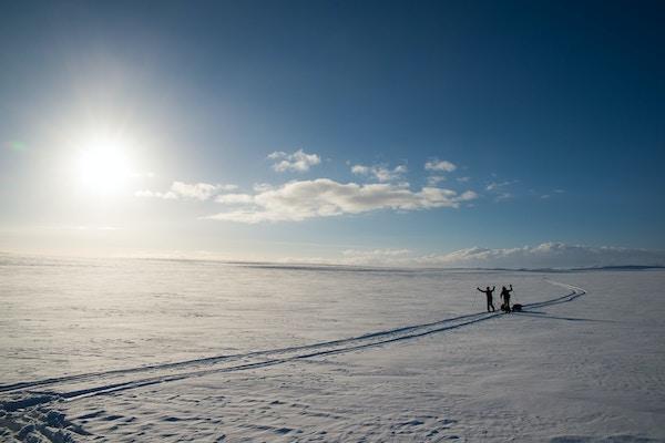 To mennesker på skitur i solnedgangen på Finnmarksvidda.