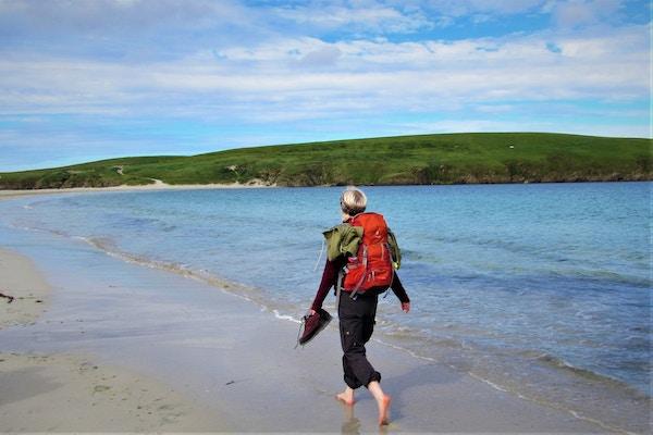 Kvinne går langs kysten på Shetland.