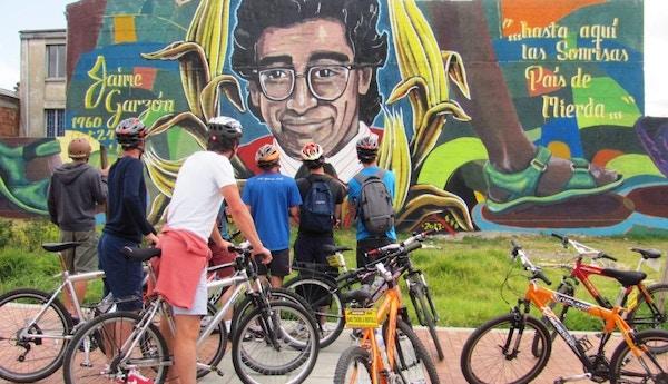 Syklister utenfor en plakat i Colombia.