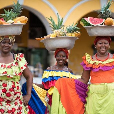 Tre fargerike damer med fruktfat på hodet